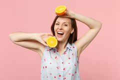 Cheerful young girl in summer clothes holding two halfs of fresh ripe orange fruit isolated on pink pastel wall stock photography
