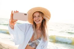 Cheerful young girl in summer hat. And swimwear spending time at the beach, taking a selfie with outsretched hand Royalty Free Stock Photography