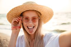 Cheerful young girl in summer hat and swimwear. Spending time at the beach, taking a selfie Stock Photo