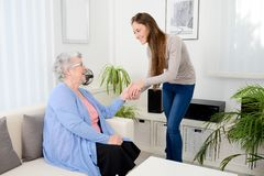 Cheerful young girl taking care of old senior woman at home. Cheerful young girl taking care of an old senior women at home stock photography