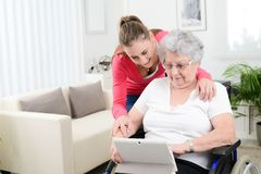 Cheerful young girl teaching internet with computer tablet and sharing time with an old senior woman on wheelchair Royalty Free Stock Images