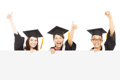 Cheerful young graduate students raise hands Stock Photos