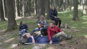 Cheerful young group of teen campers in the woods having fun playing guitar singing and taking selfie - stock video