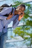 Cheerful young guy with back talking on cell phone Stock Image