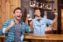 Cheerful young guy and bartender in sport pub Stock Photos