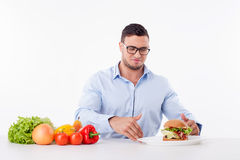 Cheerful young guy is denying unhealthy food Royalty Free Stock Images