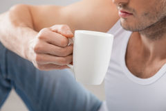 Cheerful young guy is drinking hot tea Stock Image