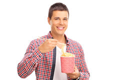 Cheerful young guy eating Chinese food Stock Image