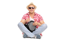 Cheerful young guy playing a doumbek Royalty Free Stock Photo
