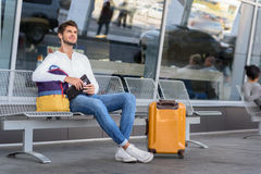 Cheerful young guy preparing for trip. Happy male tourist is ready for journey. He is sitting near at airport outdoors near suitcase and smiling. Man is holding Stock Photos