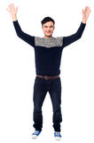 Cheerful young guy raising his arms Royalty Free Stock Photo
