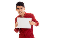 Cheerful young guy in red shirt with empty placard in hands posing isolated on white background Stock Photos