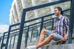 Cheerful young guy relaxing on staircase with skateboard. Happy male skateboarder is resting on stairs and smiling. He is sitting and carrying skate. Man is Royalty Free Stock Photo