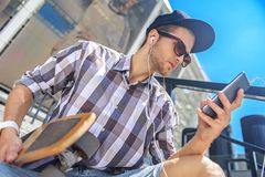 Cheerful young guy resting with skate and phone. Thoughtful male skater is enjoying music from smartphone. He is wearing headphones and looking at gadget with Stock Photography