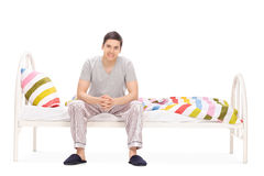 Cheerful young guy sitting on a bed Stock Photography