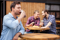 Cheerful young guy is swigging lager in bar Stock Photos