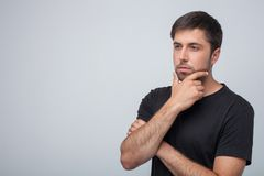 Cheerful young guy is thinking about his life stock images