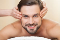 Cheerful young guy is visiting beauty salon Stock Photos