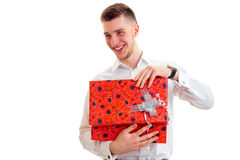 Cheerful young guy in white shirt open a red gift in his hands Stock Photos