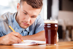 Cheerful young guy is working in pub Royalty Free Stock Images