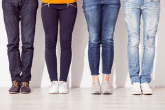 Cheerful young guys and girls are waiting. Close up of legs of four men and women standing on floor Stock Photos