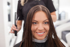 Cheerful young hairdresser is cutting hair of her Royalty Free Stock Images