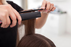 Cheerful young hairdresser in making female hair Royalty Free Stock Image