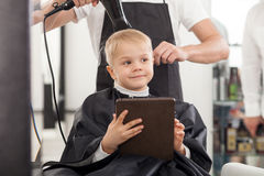 Cheerful young hairdresser is working with hair Stock Photos