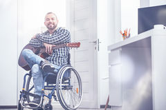 Cheerful young handicap enjoying hobby at home Stock Images