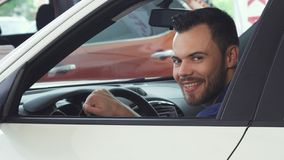 Cheerful young handsome man smiling to the camera sitting in his new car royalty free stock photography