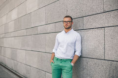 Cheerful young handsome man in sunglasses keeping hands in pockets. And looking away with smile while standing against grey background. Stylish concentrated man Royalty Free Stock Image
