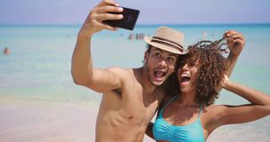 Cheerful happy couple selfies on beach. Cheerful young happy ethnic man and woman standing on sunny sandy beach and taking selfie together stock video