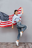 Cheerful young happy girl holding USA flag and jumping Stock Photography