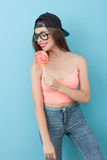 Cheerful young hipster girl is eating lollipop Stock Images