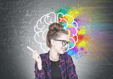 Cheerful young hipster woman, creative brain. Smiling confident young hipster woman wearing a checkered shirt, a black t shirt and glasses holding a pen and stock photo