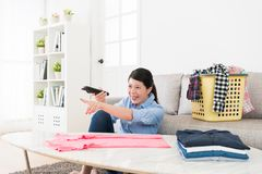 Cheerful young housewife watching funny tv program. Relaxing in living room and pointing screen feeling happy when she folding family clothing Stock Images