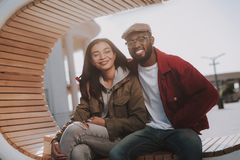 Cheerful young international couple sitting on the bench royalty free stock images