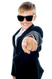 Cheerful young kid pointing towards the camera Stock Image