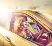 Cheerful young lady driving a limo Stock Images