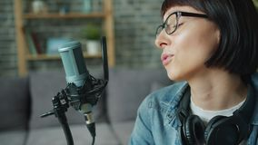Cheerful young lady talking recording audio using microphone in apartment stock footage