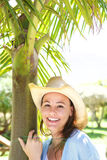 Cheerful young lady in hat standing by a tree outdoors Royalty Free Stock Images