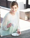 Cheerful young lady holding a cup of coffee outdoo Stock Images