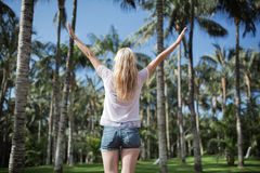 Cheerful young lady in the palm tree alley Stock Photos