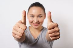 Cheerful young lady showing two thumbs up and looking at camera. Pretty woman recommending something. Recommendation concept, royalty free stock photo