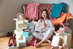 Cheerful young lady sitting on floor near sofa indoors Stock Photos