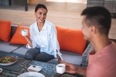 Cheerful young lady smiling to man while drinking coffee royalty free stock photos