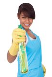 Cheerful young lady spraying cleaner liquid. Isolated on white Royalty Free Stock Photos