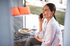 Cheerful young lady talking on the phone while having lunch royalty free stock photo