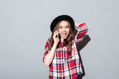Cheerful young lady talking by phone. Photo of cheerful young lady standing over grey wall wearing hat talking by phone. Looking at camera Royalty Free Stock Photos