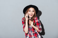 Cheerful young lady talking by phone. Picture of cheerful young lady standing over grey background talking by phone. Looking at camera Royalty Free Stock Images